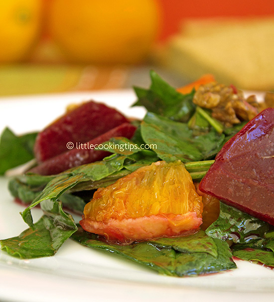 Sweet and savory green salad with spinach, beet, orange and walnuts