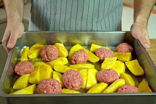 Beef meatballs and potato wedges ready to be baked in the oven