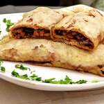 Baked crepes with ground meat and melted cheese